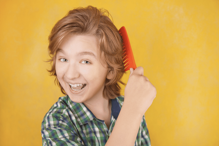 Boy combing out his hair. Lice Lifters Treatment Centers.